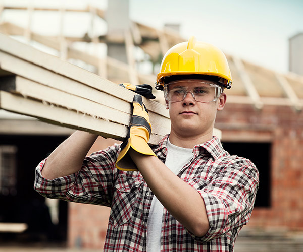 Worker in hard hat carrying wood planks